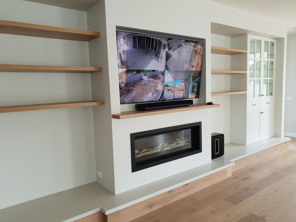 Fireplace with television above it
